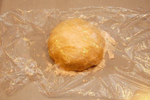 Form dough into a ball and let rest, covered in plastic on a floured surface.