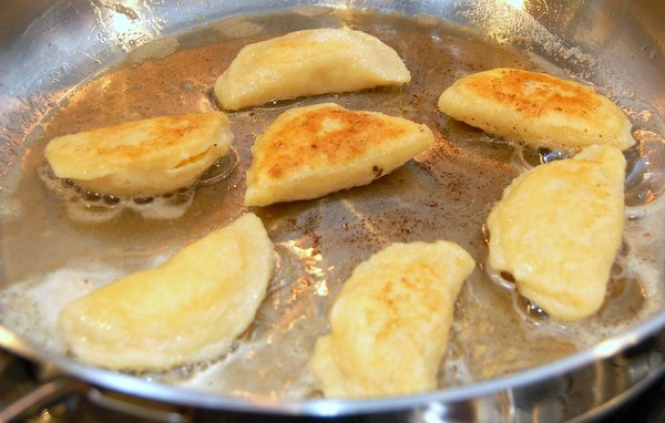 Place boiled pierogies in a hot pan with a mixture of 2 tablespoons butter and 2 tablespoons olive oil and brown.  The olive oil helps keep the butter from browning too quickly.