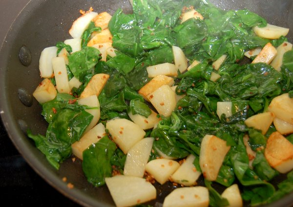 Add spinach to potatoes cook until spinach is wilted.
